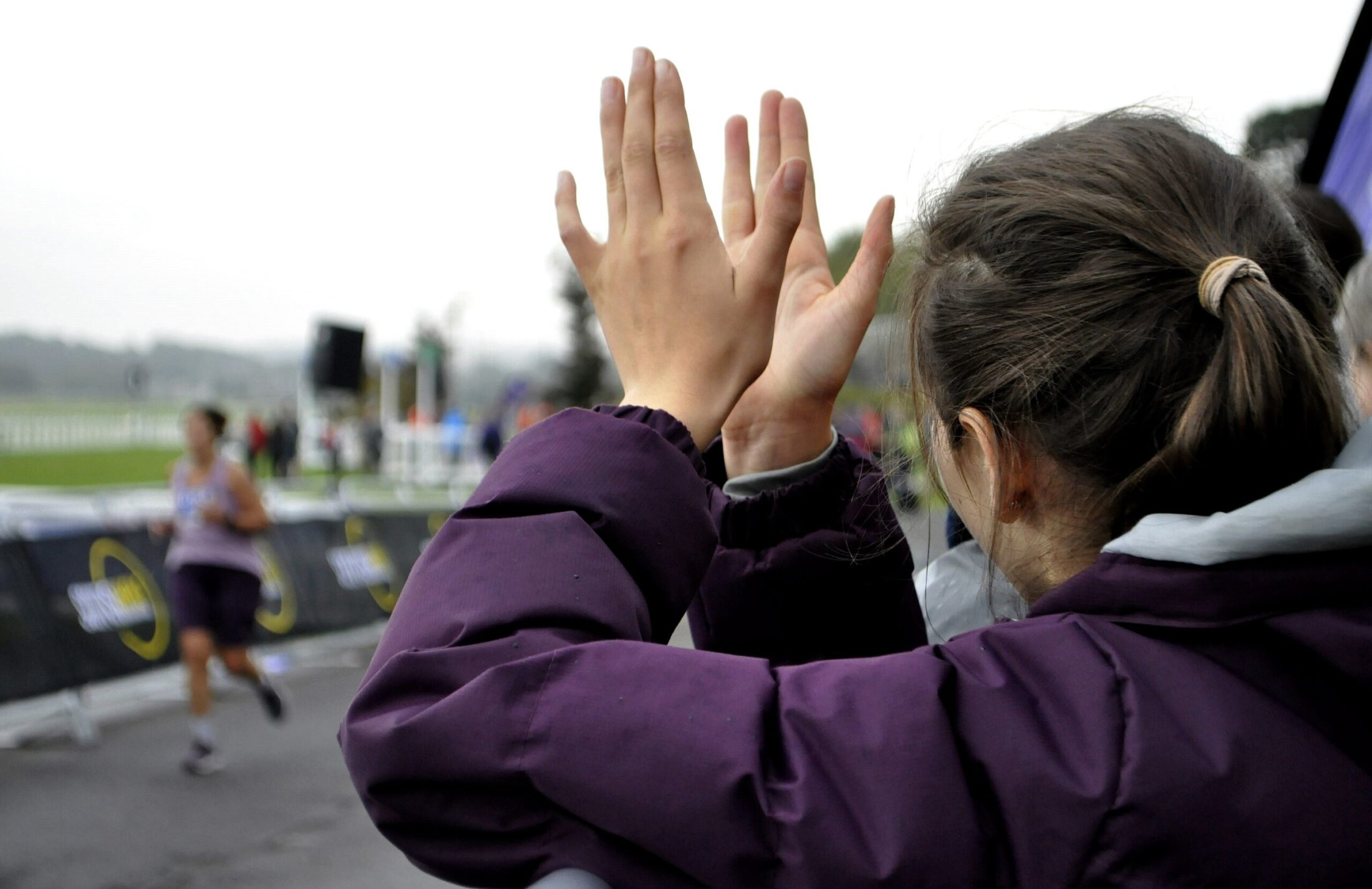 Clapping and cheering a marathon runner. From a fundraising event of a charity.