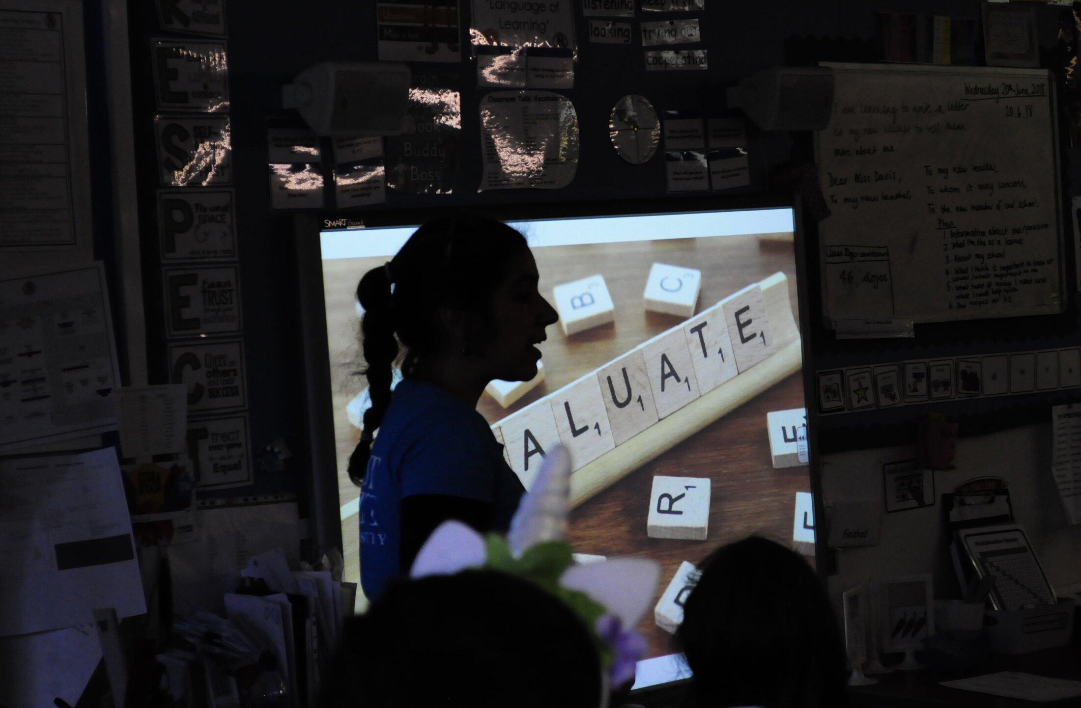A Greek migrant teaching high school students.